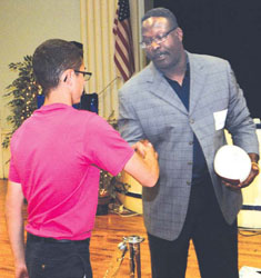 New England Patriots Hall of Famer Andre Tippett presents an autographed football to student representatives for their stellar community service at East Boston Central Catholic School as part of Catholic Schools Foundation's (CSF) annual Inner-City Scholarship Fund event.